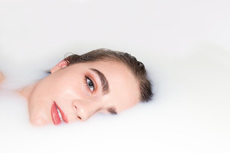 Woman with beautiful skin in a milk bath.