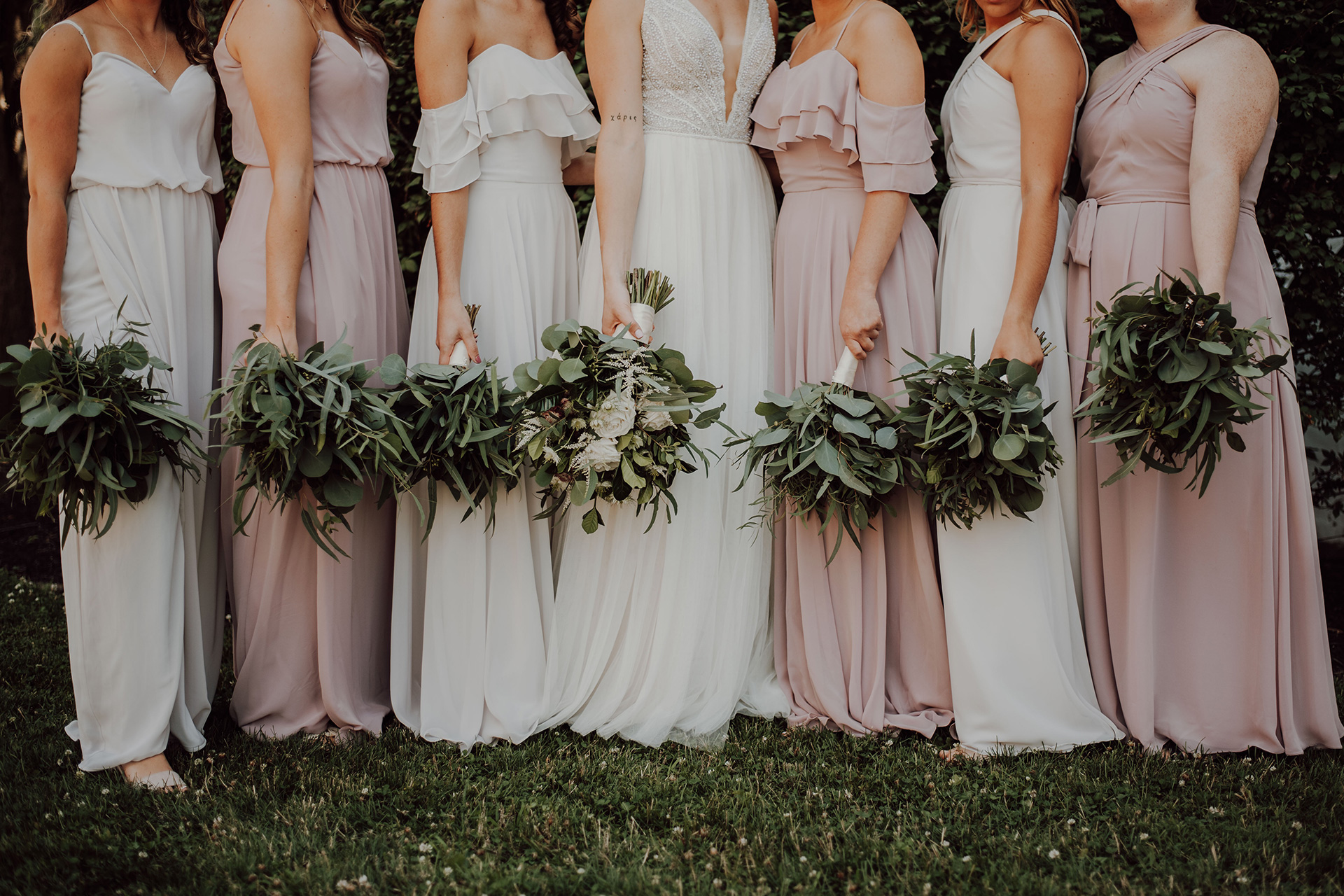 Bride standing with her bridesmaids with bouquets
