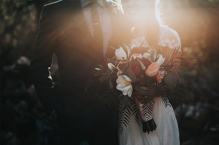 Bride and groom posing in the sunset with a beautiful bouquet.