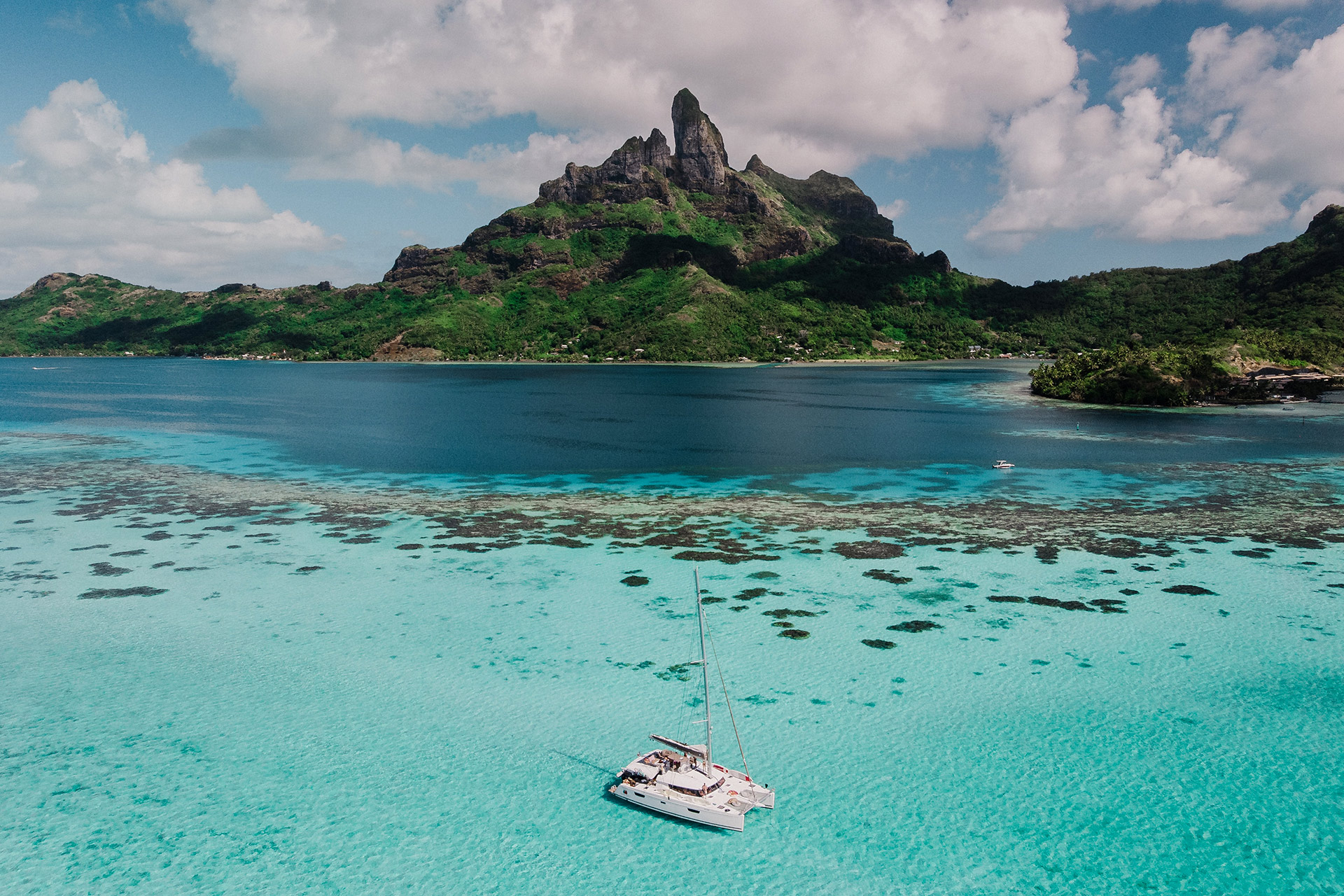 Image of an island with luxury boat floating on crystal clear water