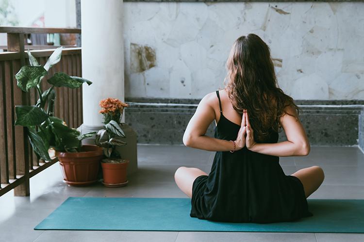 Woman sitting down on a yoga mat doing a yoga pose