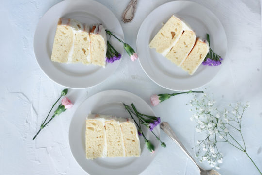 Three plates each with a slice of most vanilla cake with flowers scattered around.