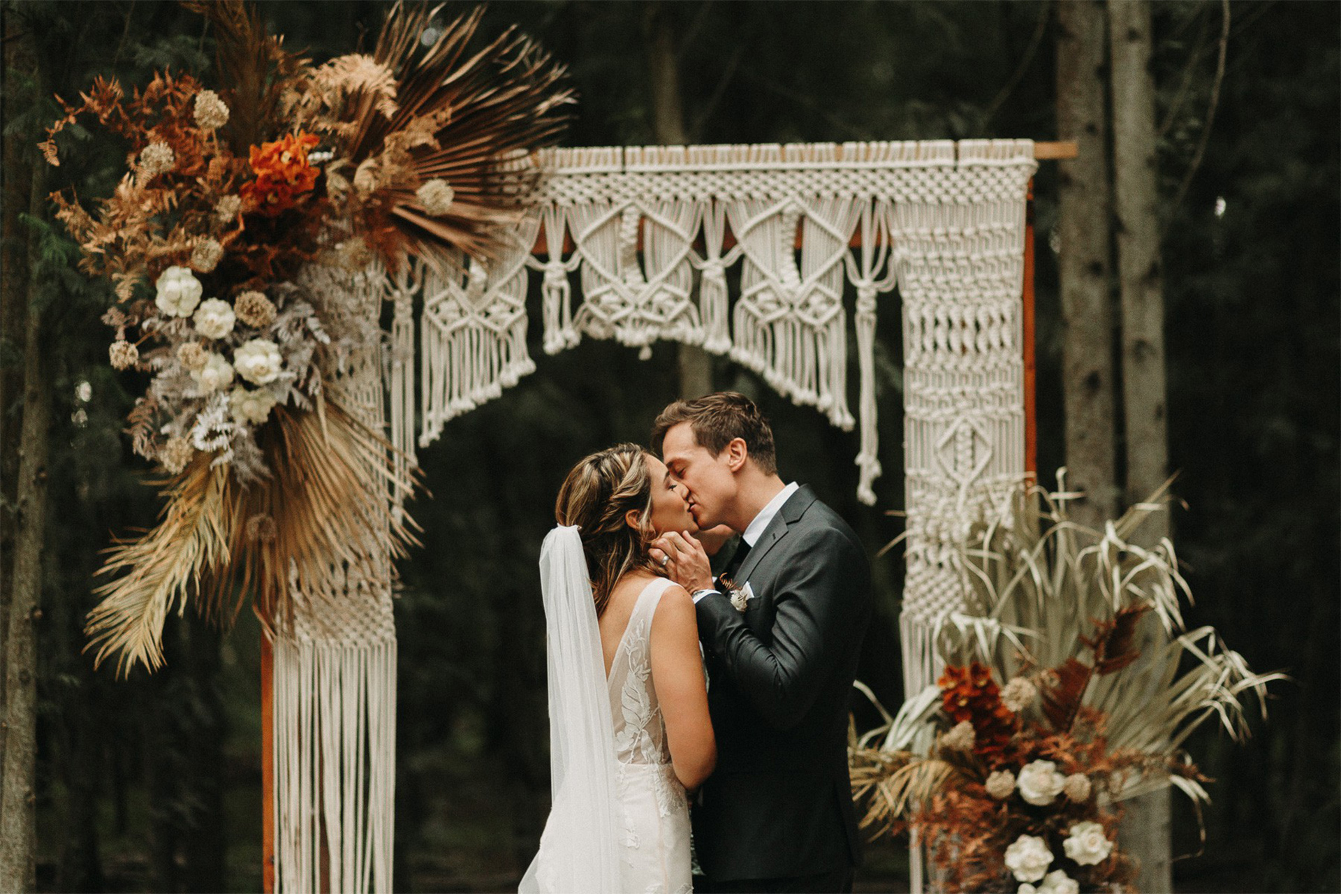 Bride and groom embracing infront of a boho style arch filled with lots of florals