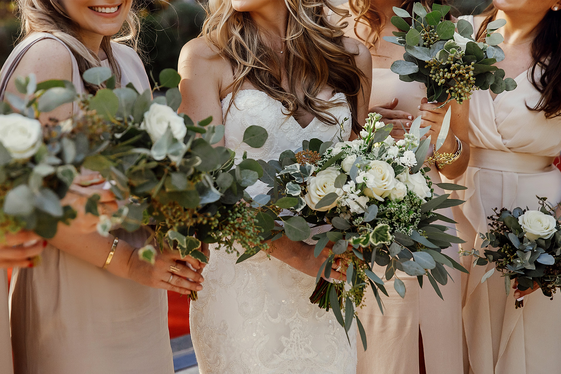 Image of bride and her bridesmaids standing in a line holding bouquets of flowers