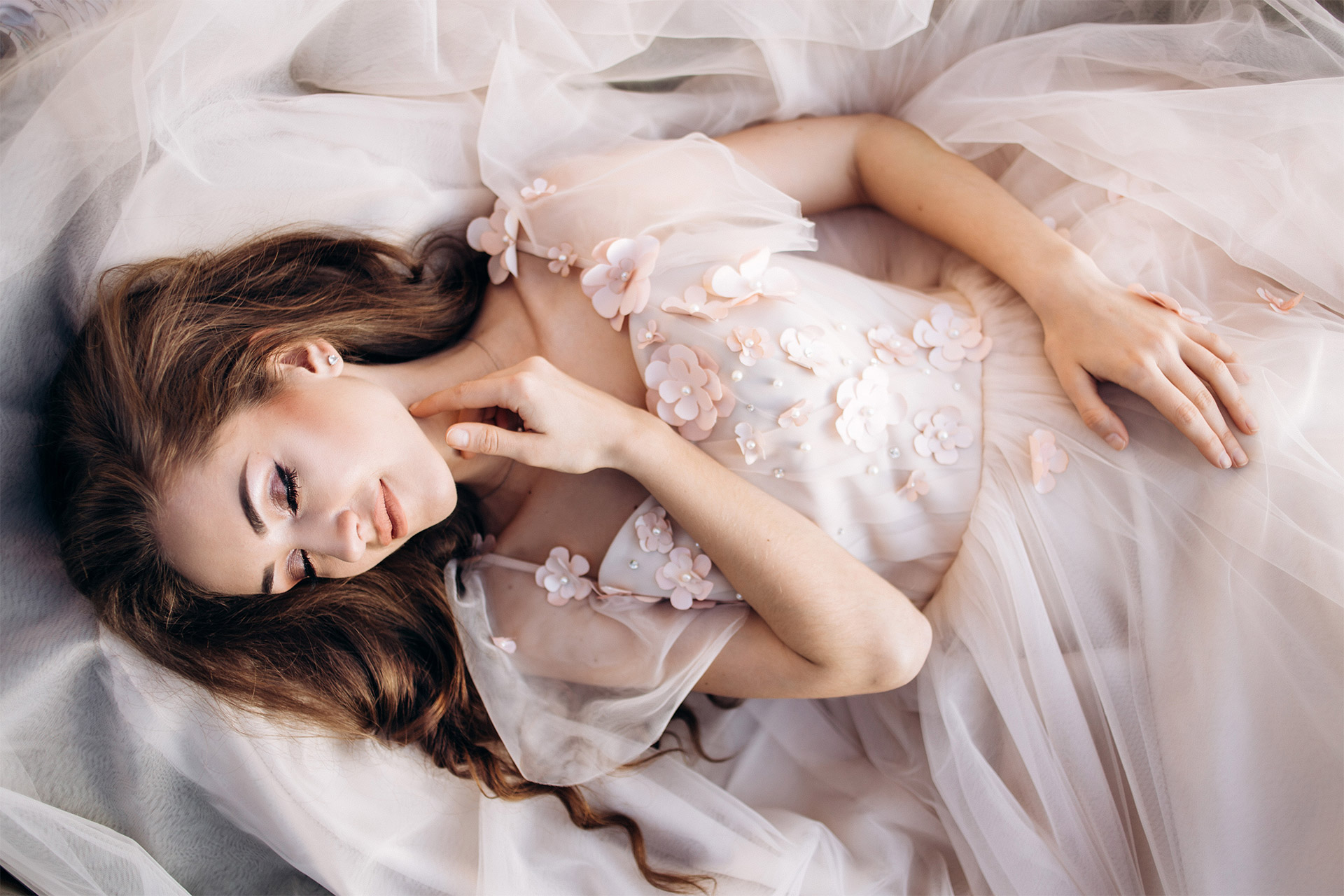 Beautiful bride wearing a wedding gown, lying on the floor.
