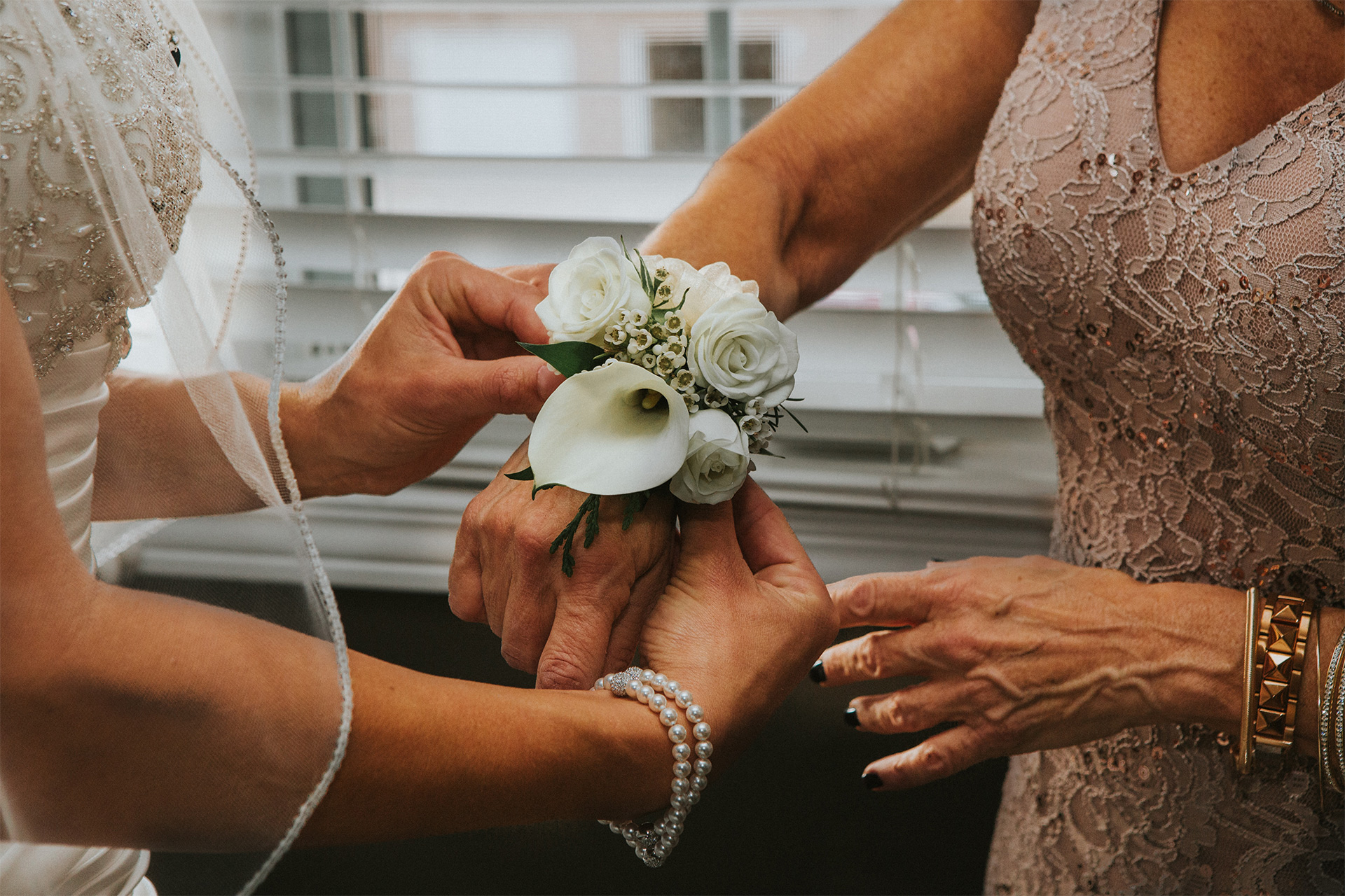 Bride helping mother of the bride put on a beautiful floral corsage on her wrist.