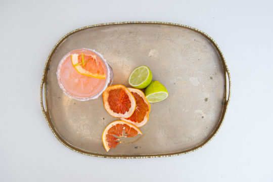 Tray with cocktail, slices of blood orange and a lemon cut in half