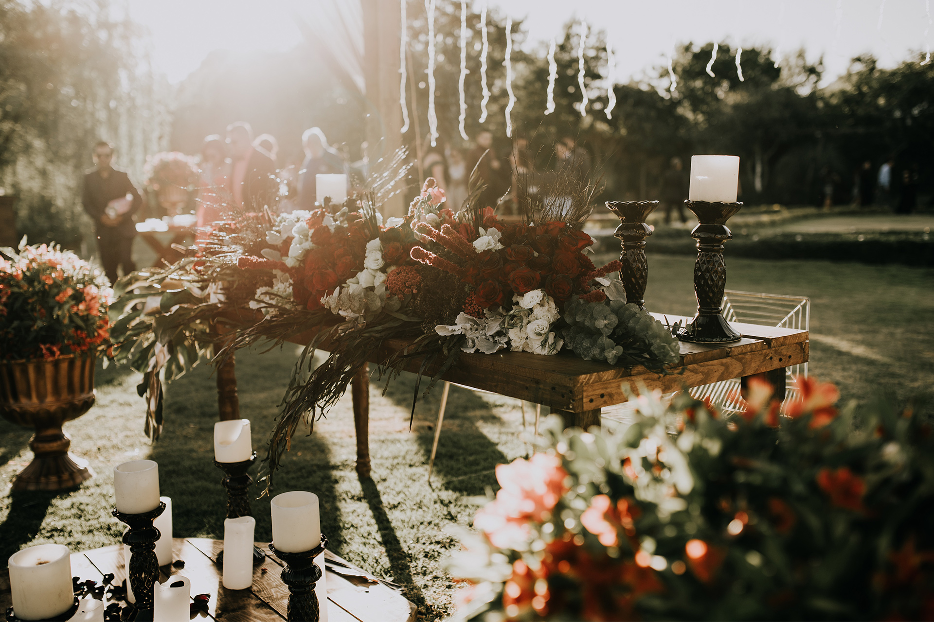Wedding table setup with lush berry toned florals and various candles outside.