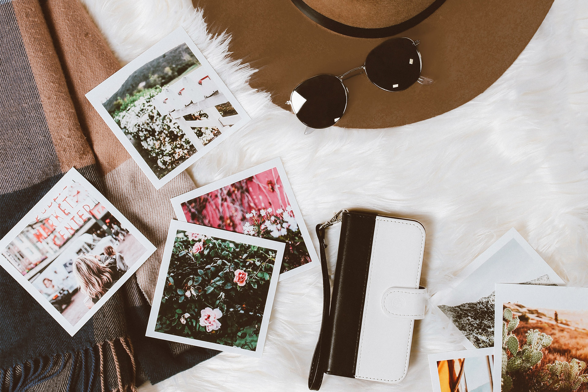 Flat lay on bed with polaroid print outs, hat, sunglasses and cellphone