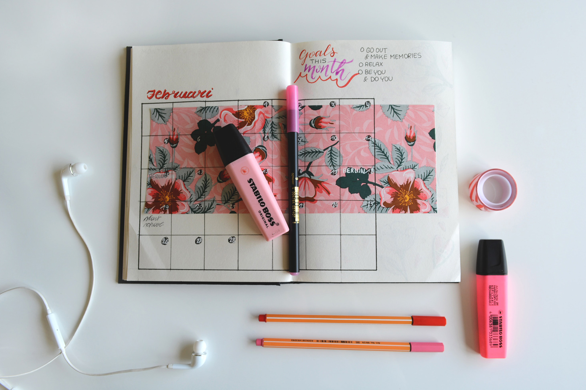 Open diary with tropical sketch with pens, highlighters and earphones flatlayed around