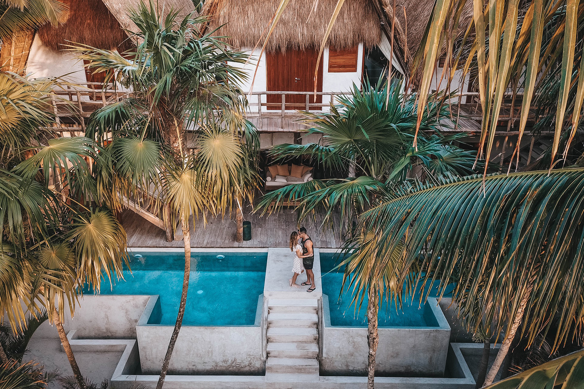 Couple embracing in a tropical destination surrounded by a pool and palm trees
