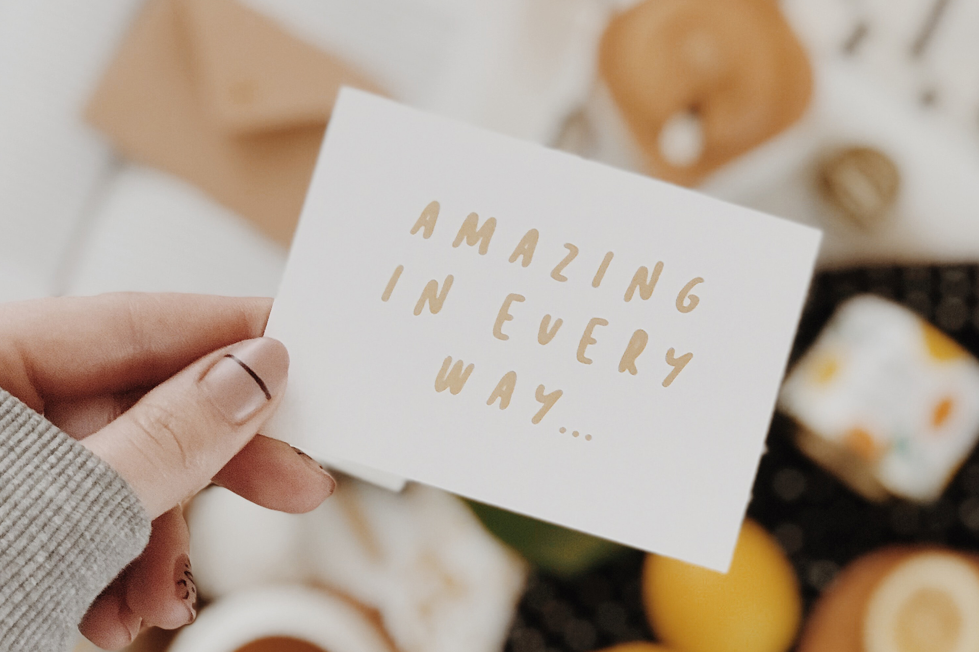Woman holding up a card that says 'amazing in every way'