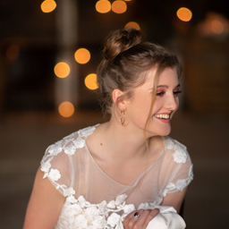 Bride holding her wedding dress and laughing
