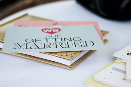 Card ontop of a book that says 'we are getting married'