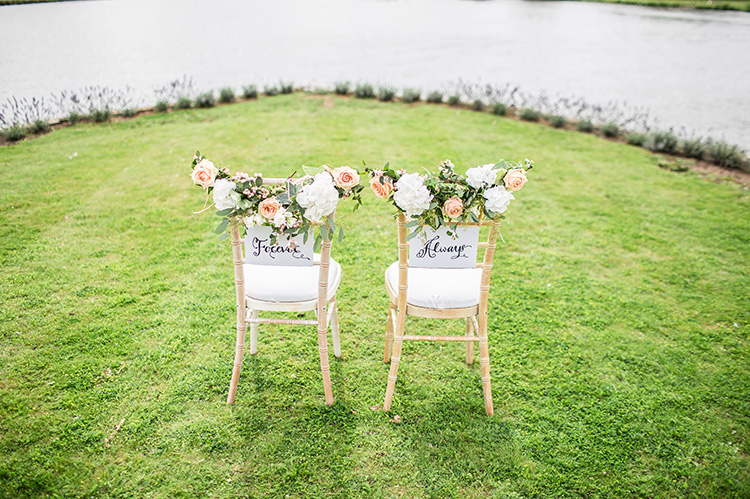 Two bridal chairs decorated with flowers overlooking a lake with signage attached to each chair that says Forever & Always