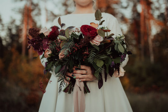 A focused image of a bride holding a lush bouquet