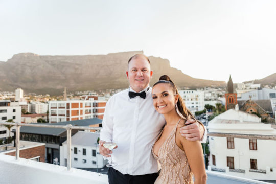 Husband and wife standing on a rooftop with cityscape in the background