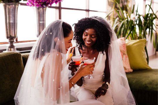 Two brides enjoying a wedding cocktail on their wedding day