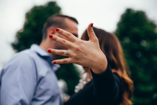 Close up shot of couple recently engaged showing her ring off to the camera.